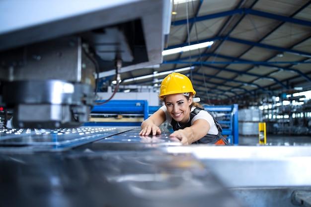 Работница фабрики в защитной форме и каске работает на промышленной машине на производственной линии Бесплатные Фотографии