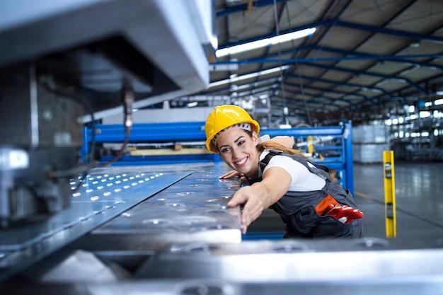 Operaio femminile in uniforme protettiva ed elmetto protettivo che opera macchina industriale alla linea di produzione Foto Gratuite