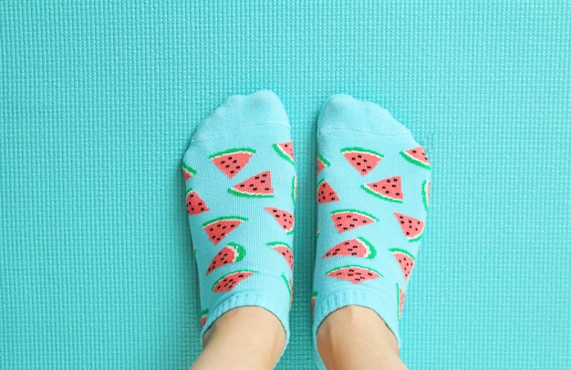 Female feet in colorful socks in watermelon print on a pastel mint background. Premium Photo