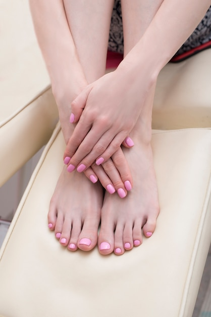 Female feet and hands with a pink manicure. beauty saloon. close-up Premium Photo