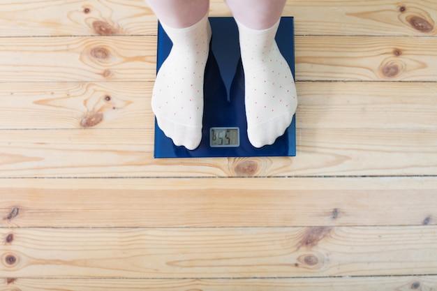 Женские ножки в носках на напольных весах Premium Фотографии