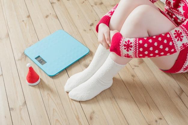 Женские ножки возле синих электронных весов для контроля веса с рождественской новогодней шапкой на деревянном полу Premium Фотографии