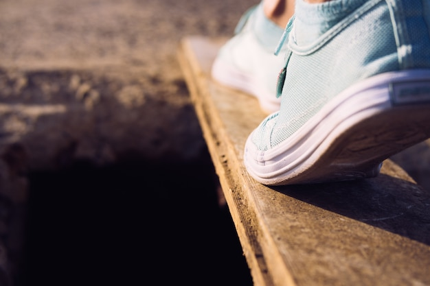 Female feet in sneakers walking on a narrow board above a large pit Premium Photo