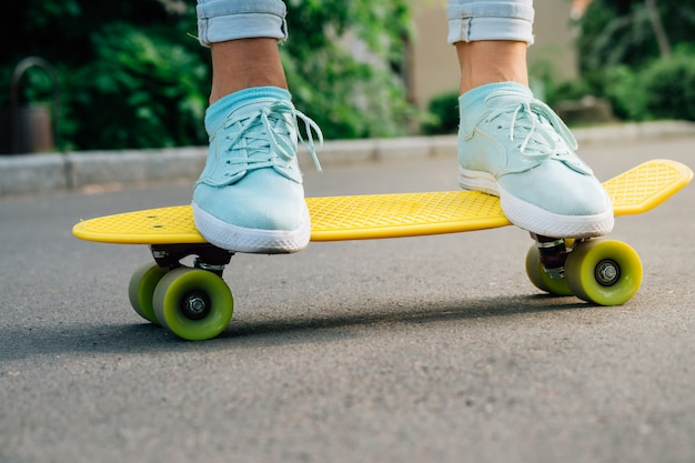 Female feet in sneakers on a yellow skateboard Premium Photo