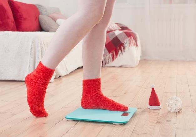Женские ножки, стоящие на синих электронных весах для контроля веса в красных носках с рождественским украшением Premium Фотографии