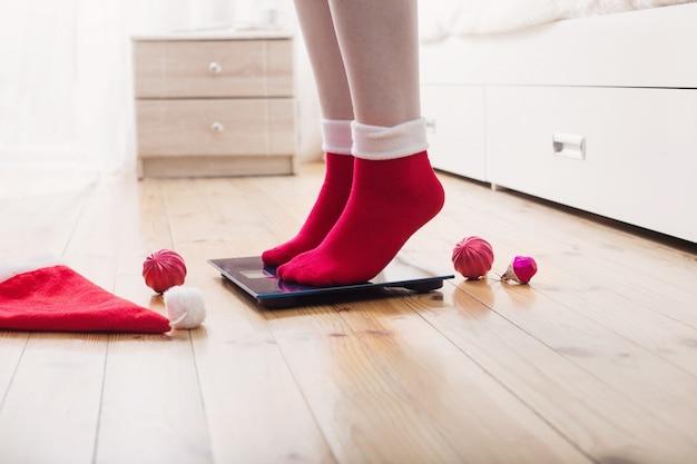 Женские ножки, стоящие на электронных весах для контроля веса в красных носках с новогодним украшением Premium Фотографии