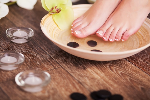 Female feet with drops of water, spa bowls, towels, flowers and candles. Premium Photo