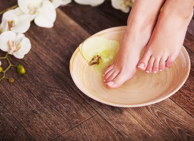 Female feet with drops of water, spa bowls, towels Premium Photo