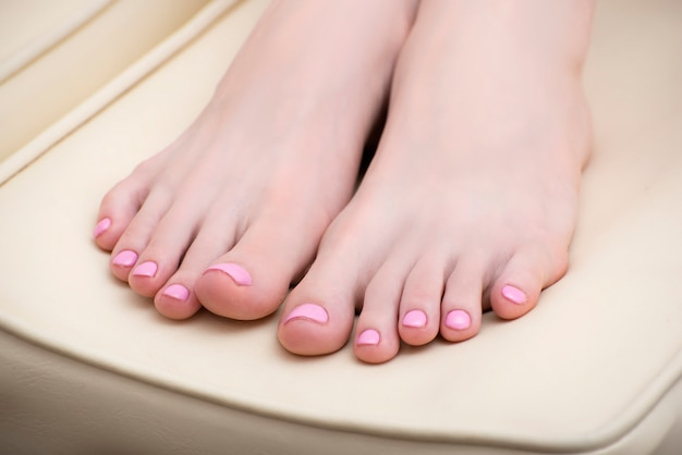 Female feet with a pink pedicure Premium Photo