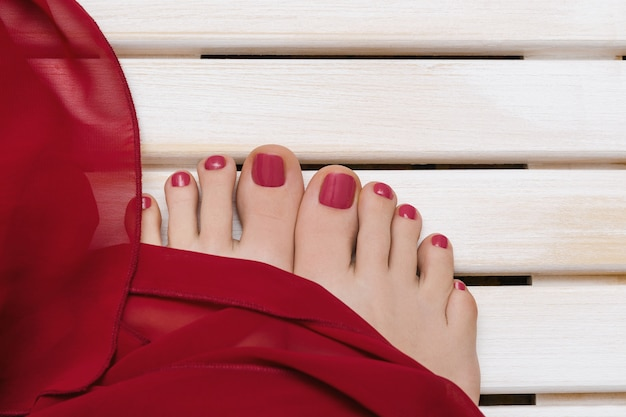 Female feet with red pedicure on wooden board Premium Photo