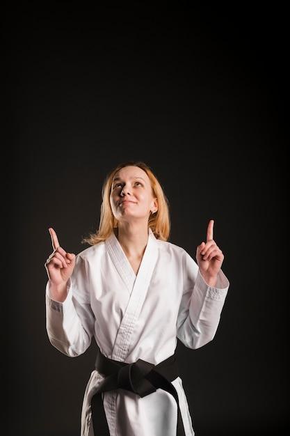 Female fighter pointing up medium shot Free Photo