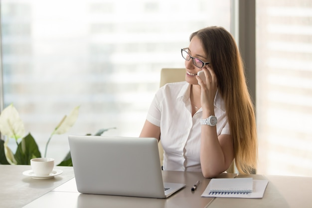 Female financial adviser consults clients by phone Free Photo