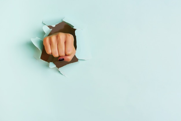 Female fist punching through blue paper background. war, struggle, conflict, feminist concept. Premium Photo