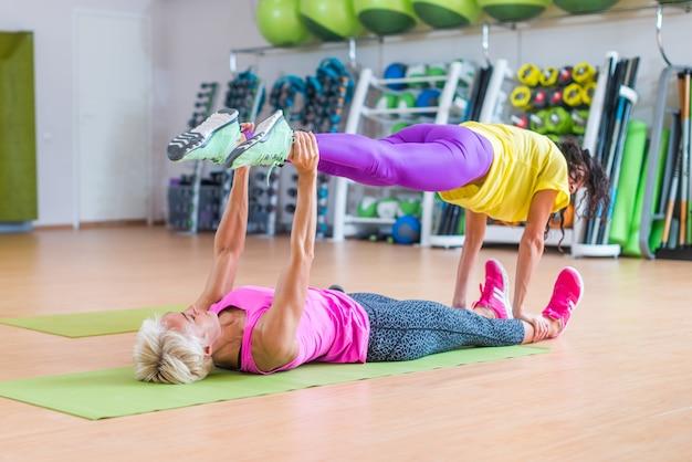 スポーツセンターで彼女の上に別の足を保持しているフロアマットに横たわっているヨガの練習をしている女性のフィットネスモデル Premium写真