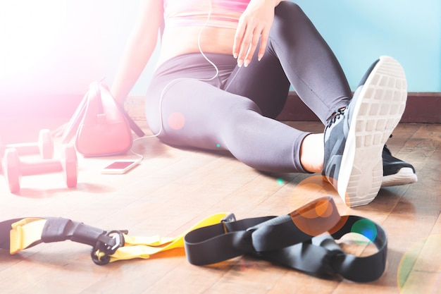 Female fitness resting and relaxing after workout. woman sitting down on wood floor. sport, fitness, healthy lifestyle concept Free Photo