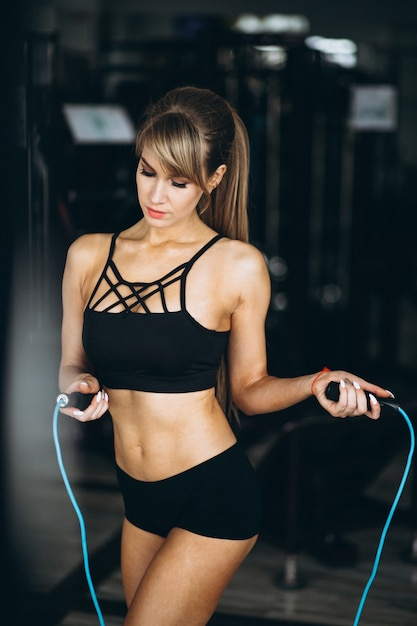Female fitness trainer at the gym with the jump rope Free Photo