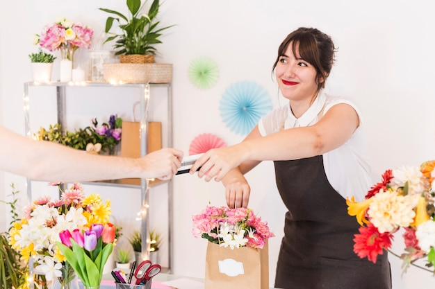 Female florist accepting credit card from her customer Free Photo