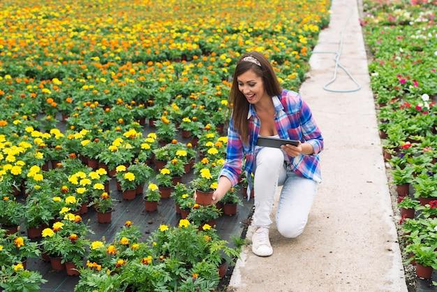 Fiorista femminile che controlla la freschezza delle piante in vaso nel centro del giardino Foto Gratuite