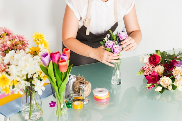 Female florist hand putting flowers in vase on glass desk Free Photo