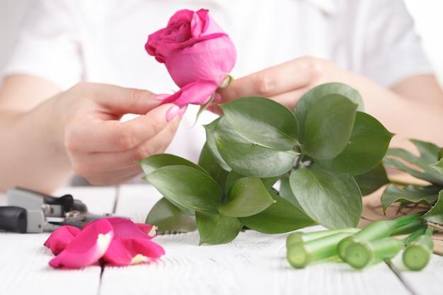 Женский флорист делает букет на рабочем столе Premium Фотографии