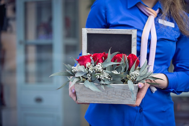 Female florist promoting a mixed flower basket. Free Photo