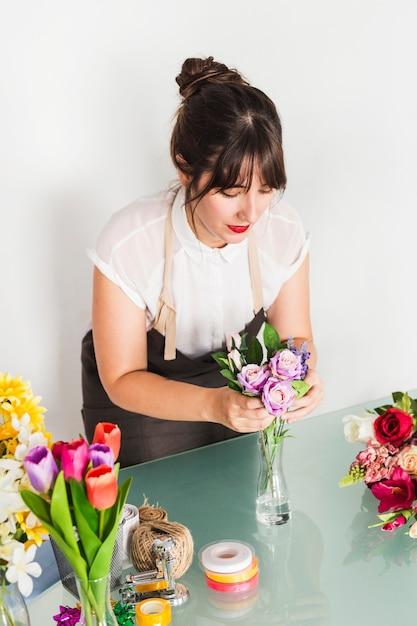 Female florist putting flowers in vase Free Photo