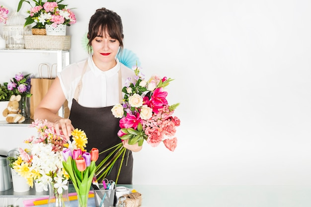 Female florist sorting flowers in floral shop Free Photo