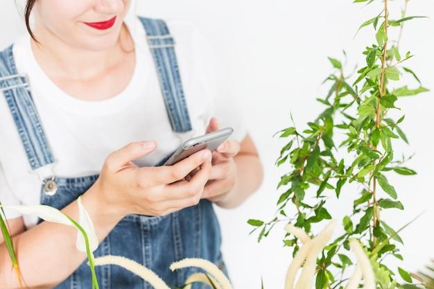 Female florist using mobile phone near plants Free Photo