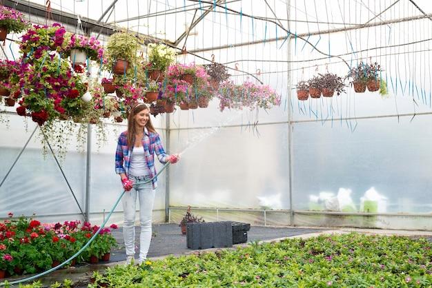温室で植物にスプレーして水をまく女性の花屋労働者 無料写真