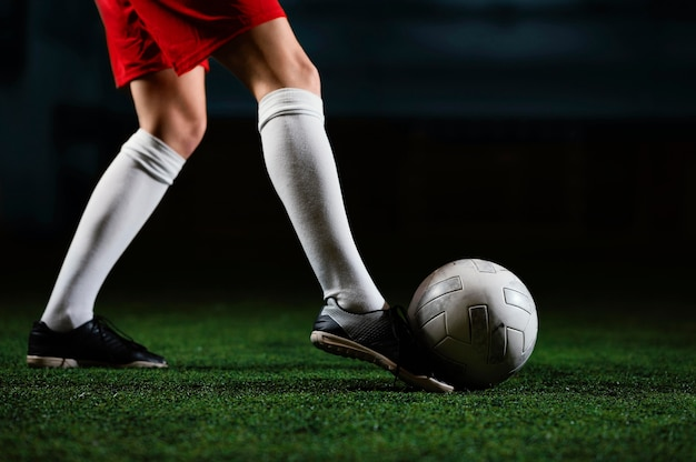Женский футболист ногами мяч рядом u Бесплатные Фотографии