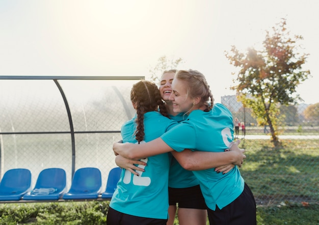 Female football players embracing each other Free Photo