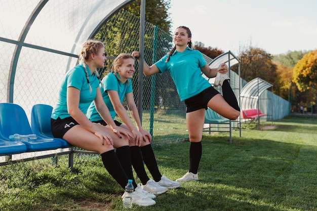 Female football players sitting on a bench Free Photo