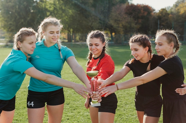 Female football team holding a trophy Free Photo