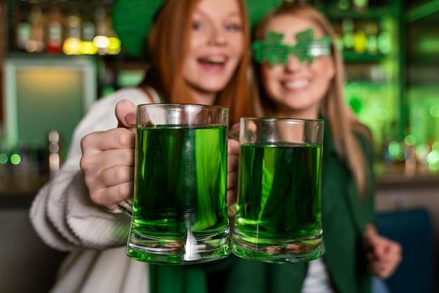 聖を祝う女性の友人。バーでドリンクを飲みながらパトリックの日 Premium写真