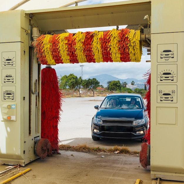 Female friends driving car for washing while traveling Free Photo