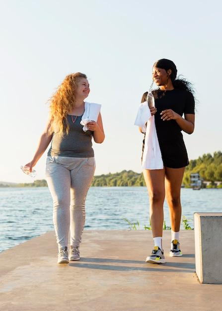 Подруги вместе тренируются у озера Бесплатные Фотографии