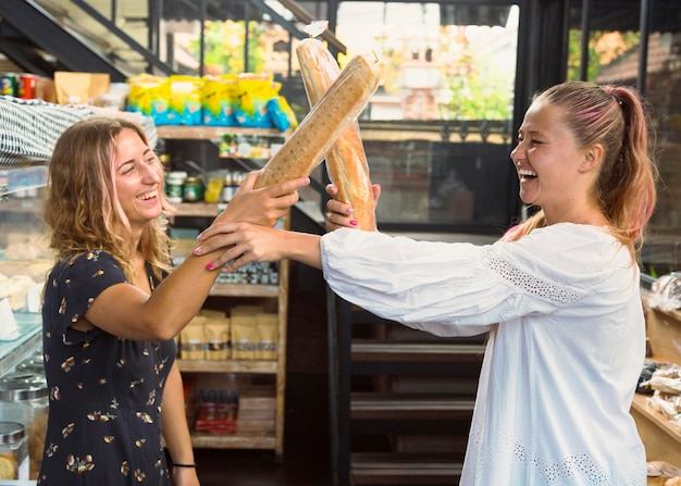 Female friends fighting with bread baguettes Free Photo