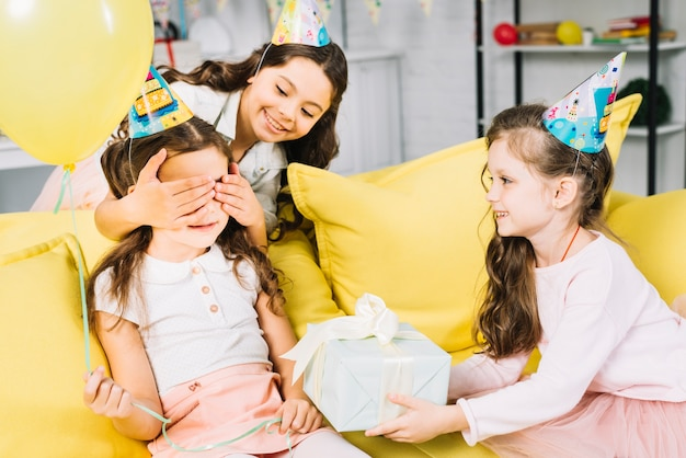 Female friends giving present to birthday girl at home Free Photo
