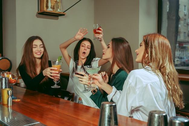 Подруги с напитками в баре. они сидят за деревянным столом с коктейлями. они чокаются Бесплатные Фотографии