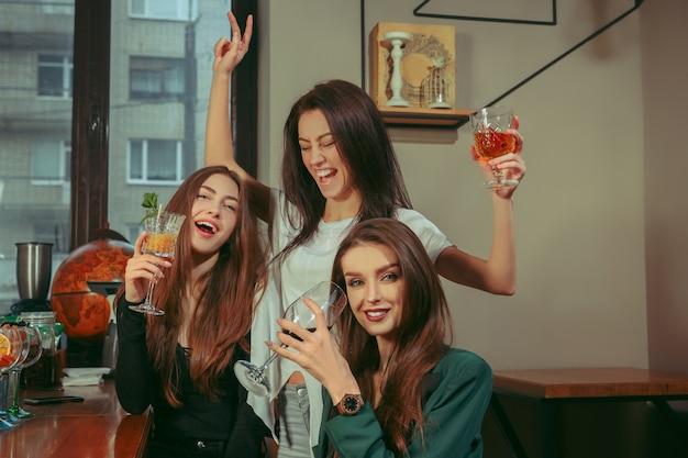 Подруги с напитками в баре. они сидят за деревянным столом с коктейлями. они одеты в повседневную одежду. Бесплатные Фотографии