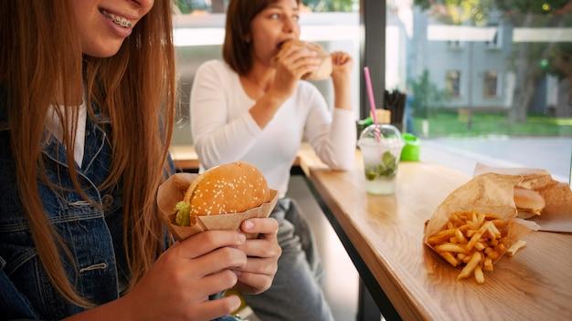 Подруги вместе с гамбургером Бесплатные Фотографии