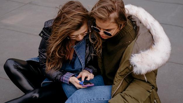 スマートフォンで屋外で一緒に楽しんでいる女性の友人 無料写真