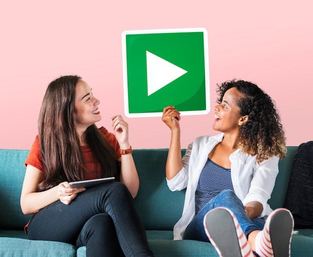 Female friends holding a play button Free Photo