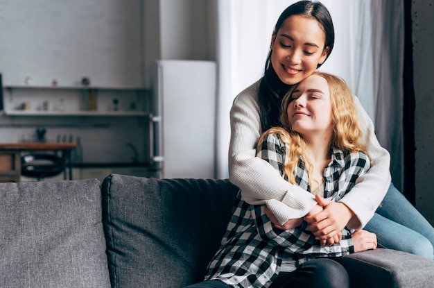 Female friends hugging tenderly at home Free Photo