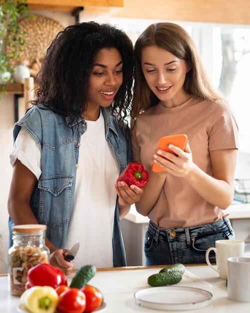 Amici femminili in cucina con smartphone e verdure Foto Gratuite