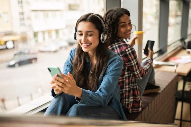 Подруги слушают музыку в наушниках Бесплатные Фотографии