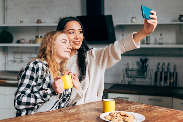 Female friends making selfies at home Free Photo