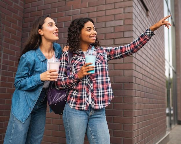 Подруги на открытом воздухе с молочными коктейлями Бесплатные Фотографии