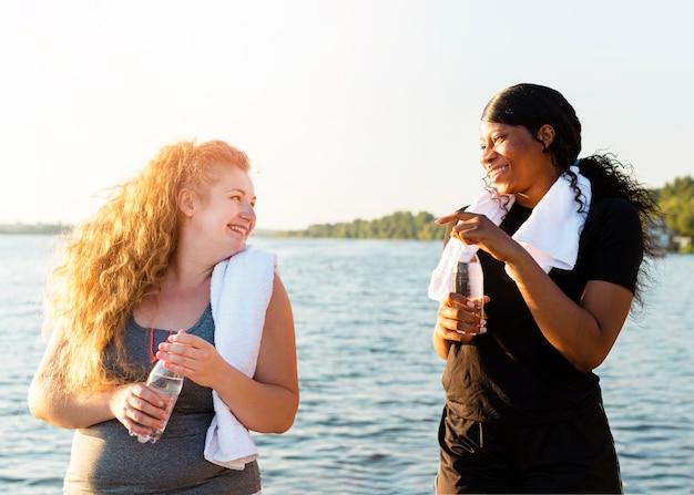 Подруги отдыхают после тренировки на берегу озера Бесплатные Фотографии