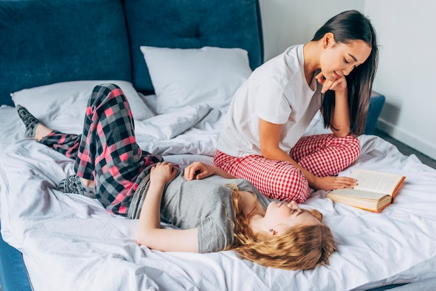 Female friends resting on bed Free Photo